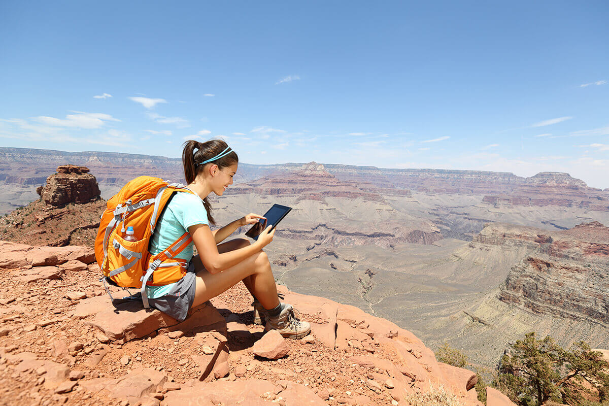 backpacker holding iPad at Grand Canyon