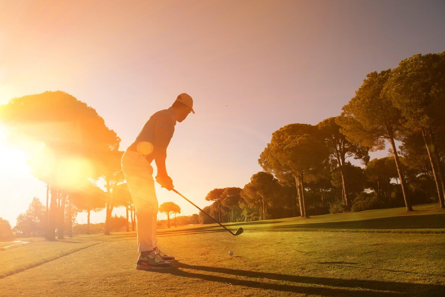 man playing golf with sunset in background